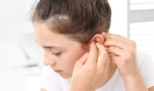 The girl assumes hearing aid